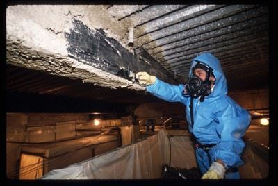 A man in a blue HAZMAT suit scraping asbestos off of a vent.